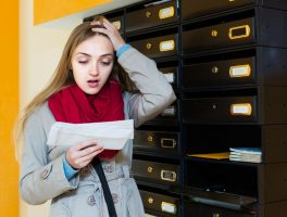 Shocked adult girl standing with letter near mail box