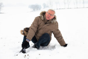 Unhappy senior man with injured painful leg on snow.